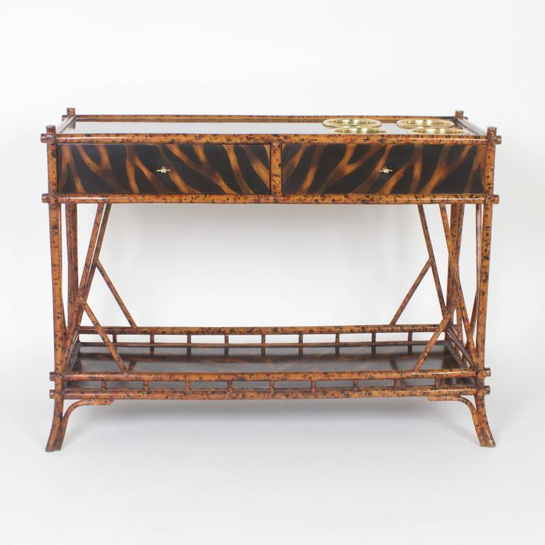 Unconventional mid century faux bamboo console or wine server having a lacquered faux tortoiseshell finish on the top, sides, back and bottom storage tray. Featuring 4 brass wine coolers set on the top. This service table is finished all the way