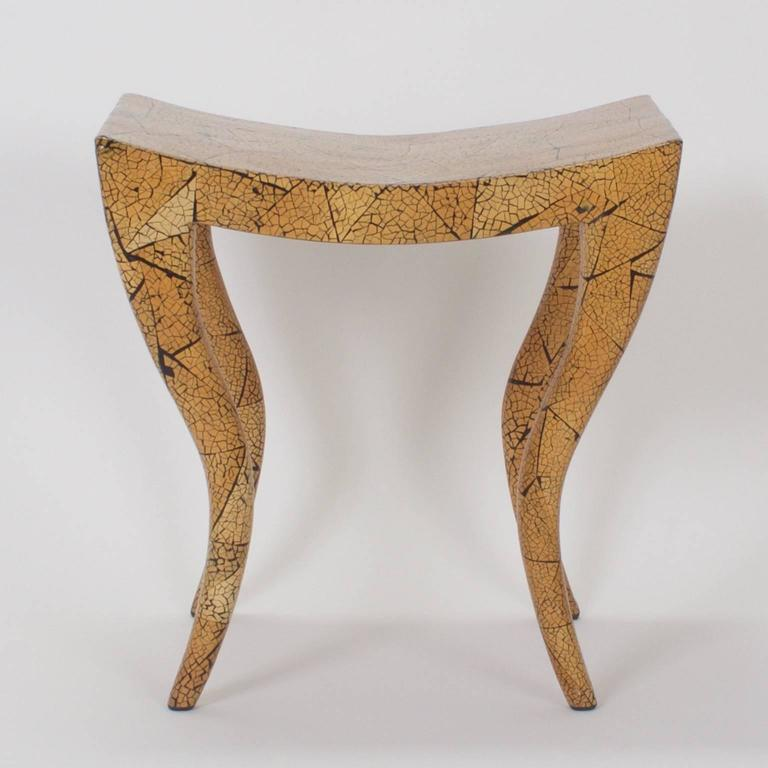 Swank Mid-Century bench or stool with a dramatic Egyptian influenced form and a hip crackled finish in variegated organic colors. Signed on a proper English brass tag