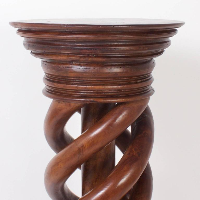 Rugged, antique pedestal with a helix twist design that defies comparison. The stand is ambitiously carved from mahogany and features a multi layered turned capital and plinth. The large-scale and expert craftsmanship make this a rare and impressive