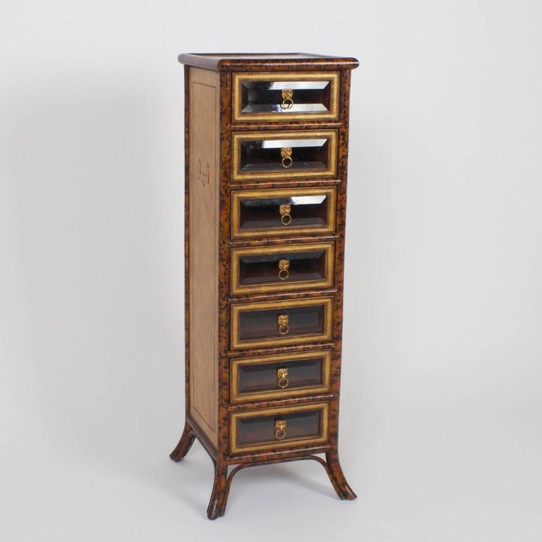 Tall, stately seven-drawer chest with a faux bamboo frame painted with a tortoise shell technique, and paneled sides with tooled leather and inset Campaign style hardware. The drawers have tooled leather borders with beveled glass and lion head