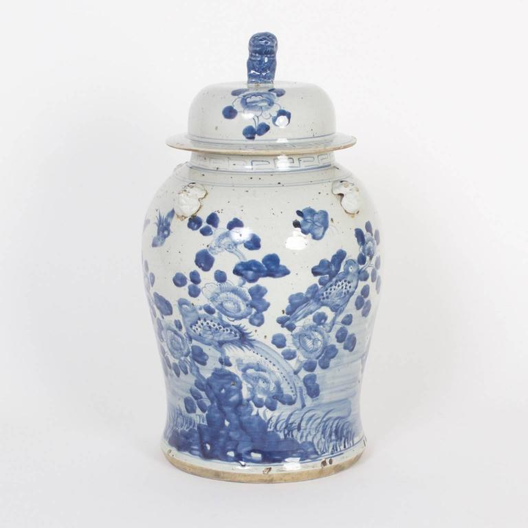 Inspired pair of Chinese export style porcelain blue and white lidded jars decorated with a soft, gracious painting technique, depicting birds, and flowers.