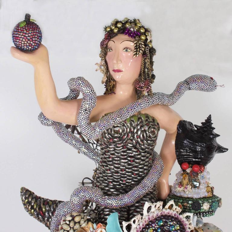 Outrageous larger than life piece of Folk Art painstakingly composed of found objects such as sea shells, beads, toys, vintage jewelry buttons, and bottle caps (to name a few). There is an obvious reference to Eve and snake, that the artist seems to