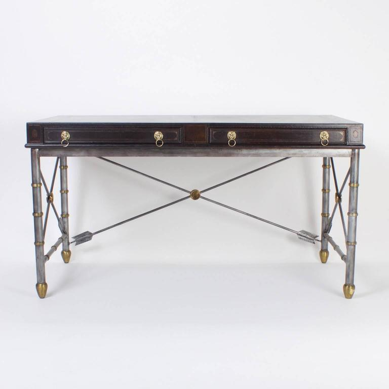 Here is a handsome Maitland Smith desk or writing table with an unusual combination of materials and influences. The top is tooled brown leather and has two drawers lined with book lining paper and lion head pulls. The base is a neoclassic design,