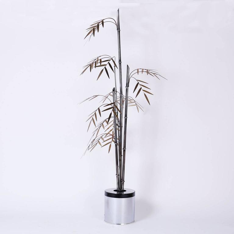 Chic, tropical palm style bamboo sculpture crafted with iron bamboo shoots in varying stages of development and copper and brass stylized branches and leaves. The canister base has a one bulb socket that can create subtle mood lighting.