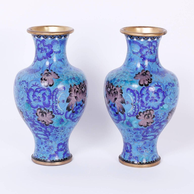 Warm and inviting pair of midcentury enamel on brass cloisonné vases with pure form and decorated with blue flowers and butterflies in a field and featuring mauve and grey peonies as highlights. An impressive combination of scale and color.