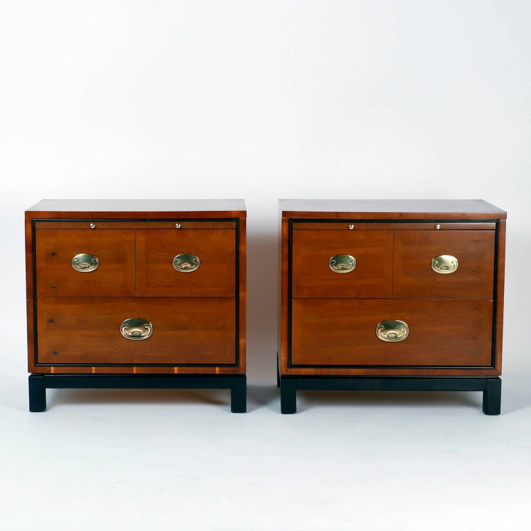 Pair of nightstands or three-drawer chests beautifully crafted with well grained walnut in a clean modern form. Featuring a pull-out tray, stylized campaign hardware and an ebonized Ming style base. Signed Hickory Manufacturing Co. in a drawer.