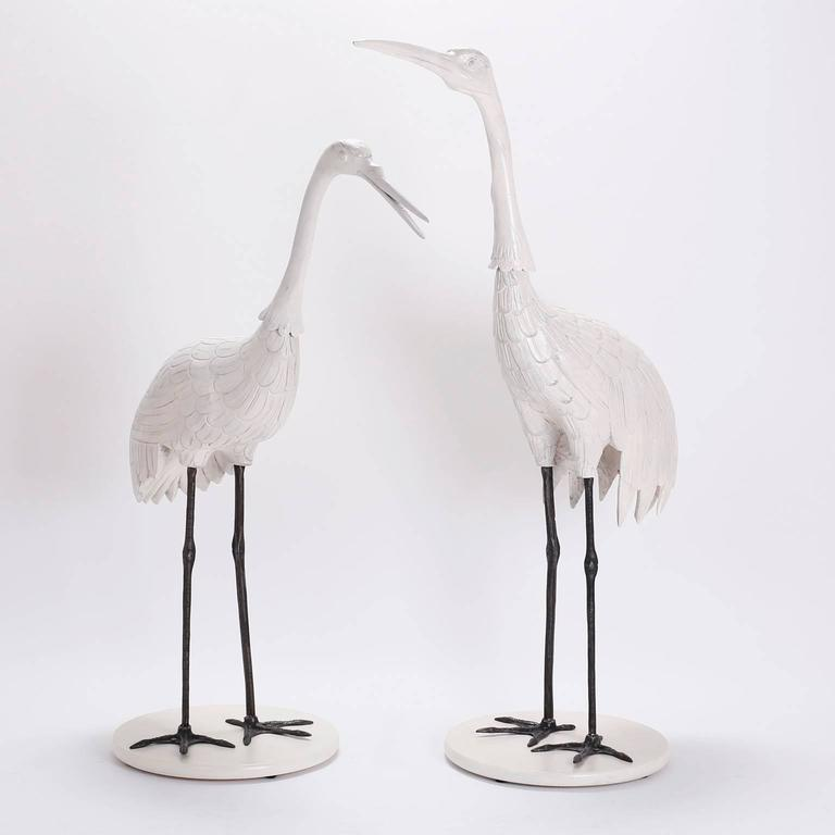 Chic, mid century pair of crane or stork sculptures crafted in carved wood with a custom lacquered finish. The legs are raw iron ,sealed for easy care, presented on round lacquered wood bases.   From left to right:  H: 50 W: 42 D: 18 H: 56 W: 38 D: