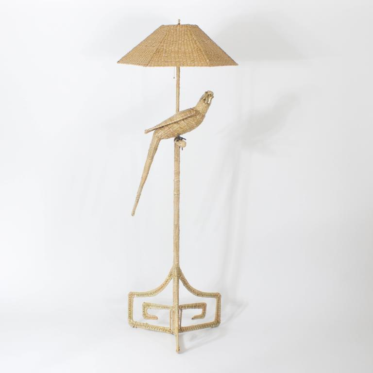 Whimsical wicker or reed Parrot floor lamp with a brass and copper beak and brass face. Featuring a matching wicker shade and a 3 legged greek key style base. All executed in a tight declined weave. Signed Mario Torres 1974 made in Mexico.