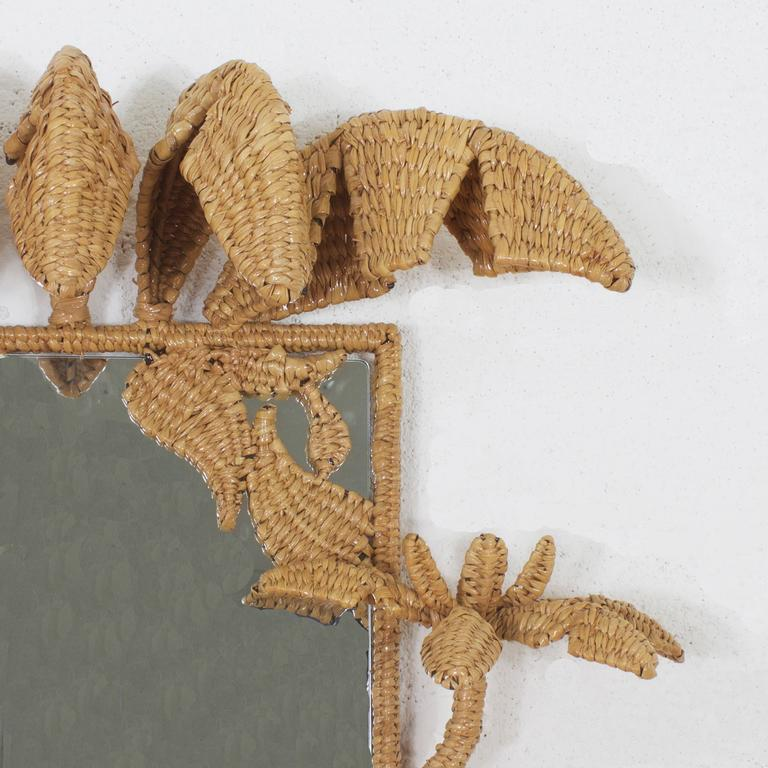 Whimsical Mid-Century Mario Torres mirrors framed with a tropical palm tree motif. Constructed of an iron frame wrapped with wicker or reed. Perfect for an island, coastal, or any home interior that can use some tropical spice. Signed Mario Torres