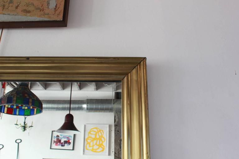 Long brass rectangular mirror.