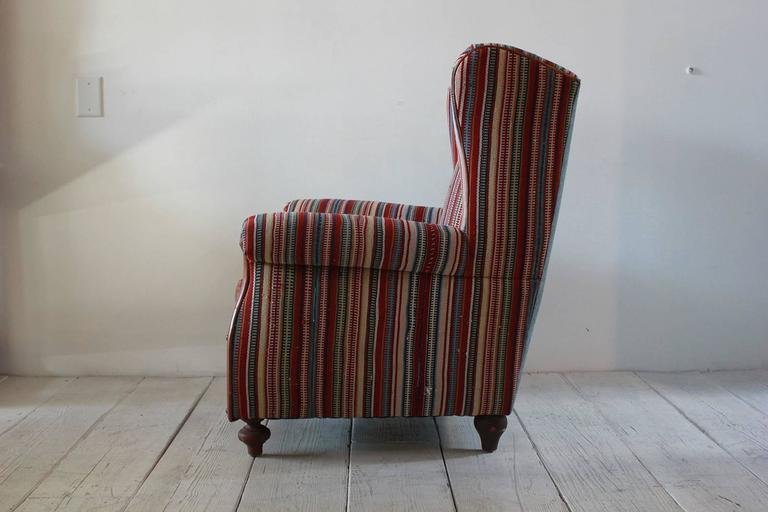 Italian Kilim wing back chair with original leather seat with reverse denim upholstered on the back with turned feet.