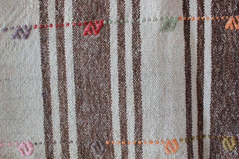 Turkish brown and natural striped rug with pink and orange details.