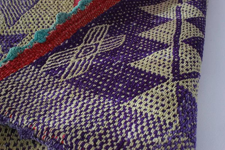 Peruvian handwoven textile with violet geometric details and red border with green accents.