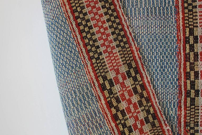 Multicolored Chinese woven rug with blue and red stripes.