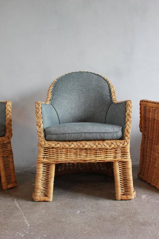 Set of four oversized wicker dining chairs upholstered in reverse denim.