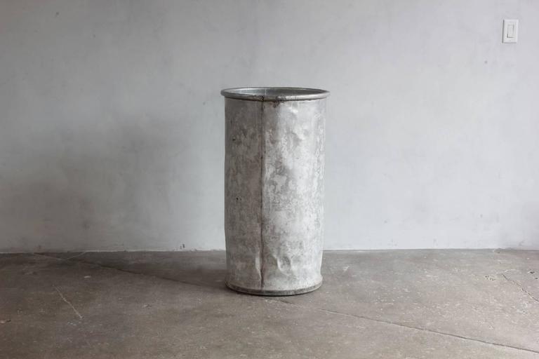 Tall galvanized cylindrical bin.