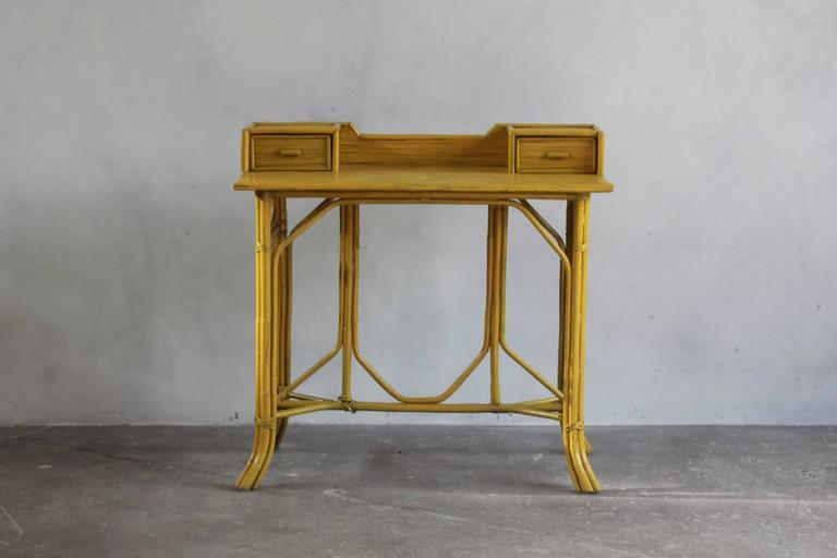 Yellow painted bamboo writing desk with two drawers.