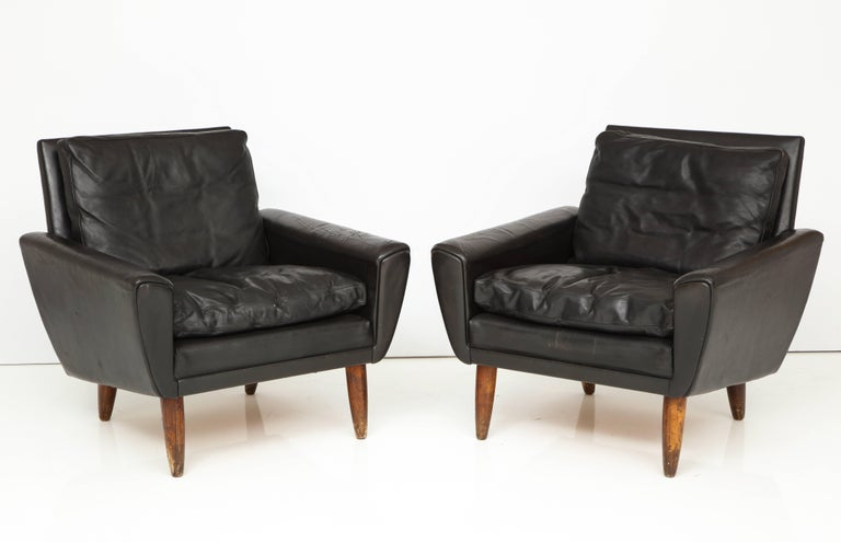 Pair of midcentury black leather chairs from France.