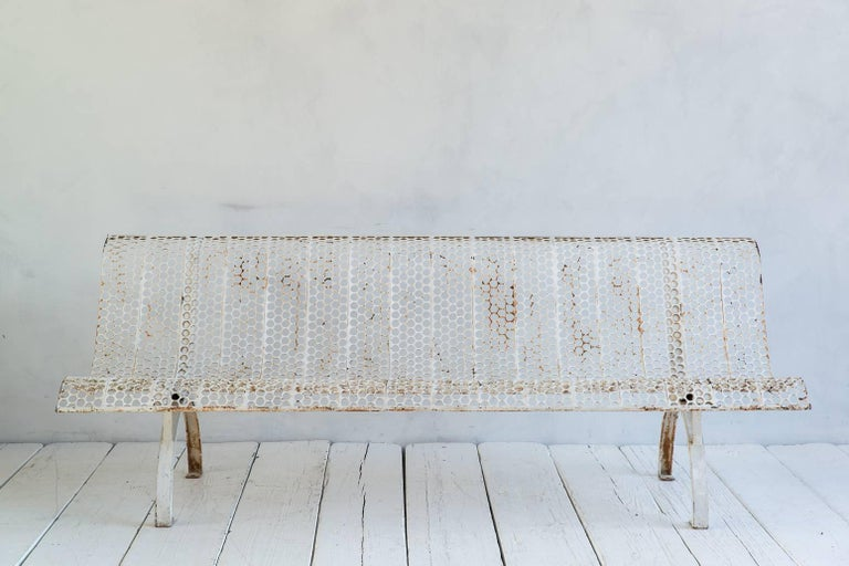 White armless metal perforated bench with aged patina.