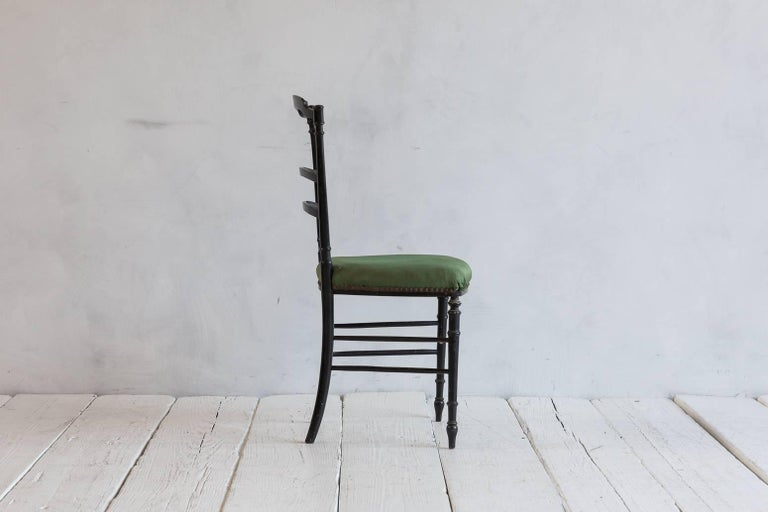 French chiavari black framed chair upholstered in original green fabric with nail heads.