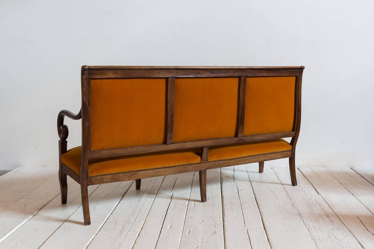 French mahogany opened framed orange velvet settee with curved arm detail with four legs.
