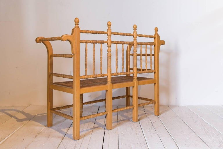 Early 20th Century Edwardian Style Light Oak Spindle Bench with Rush Seat and Curved Arms For Sale