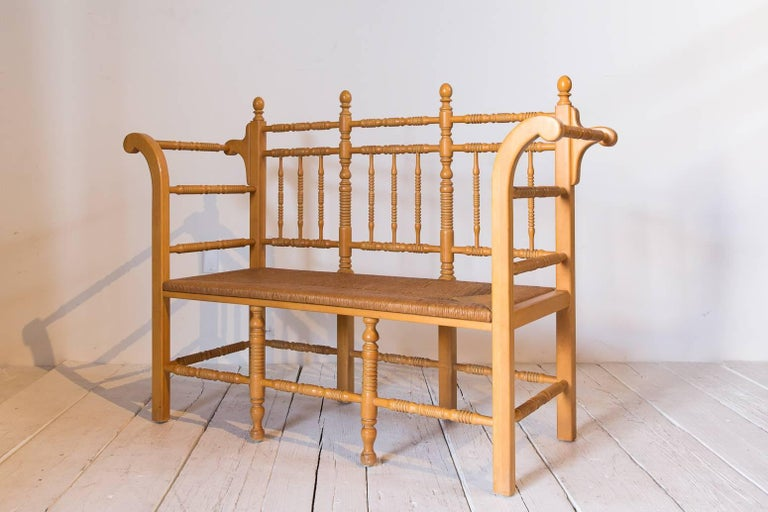 Edwardian style light oak spindle bench with rush seat and curved arms.
