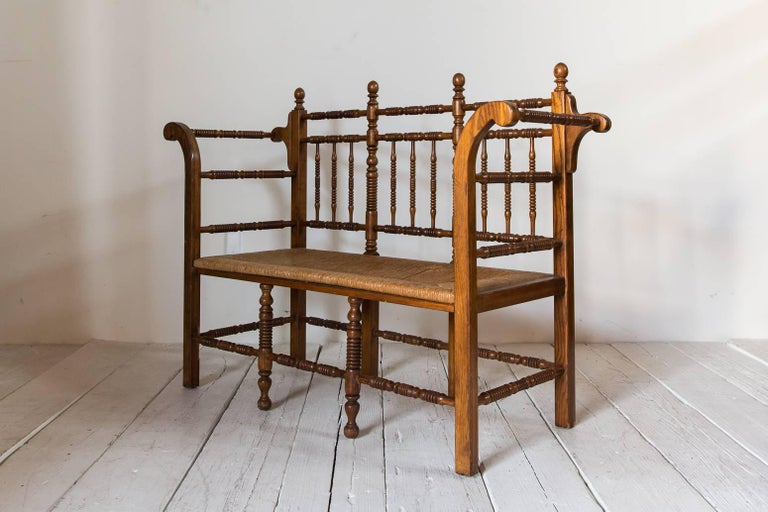 Early 20th Century Dark Oak Edwardian Spindle Bench with Rush Seat For Sale