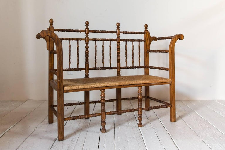 Dark oak Edwardian spindle bench with rush seat.