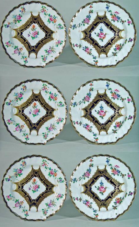 Chelsea Porcelain plates are painted in the center with a floral bouquet panel surrounded by a mazarine-blue border and fine gilt highlights of dentil work, fish scales, and flower-heads.  The fish-scale gilding is as fine as any found on British
