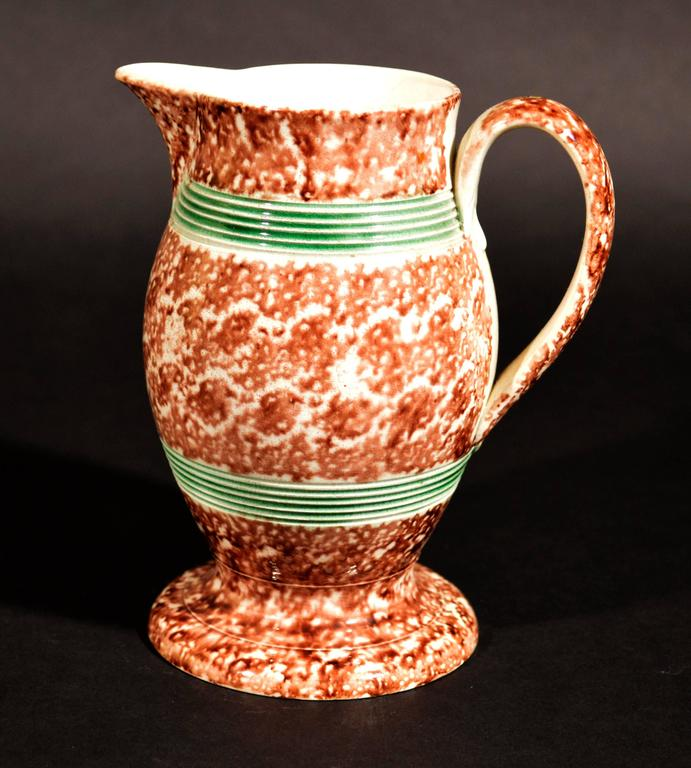 The creamware pottery Whieldon-type jug covered with a tortoiseshell glaze and with two reeded green glazed bands and standing on a splayed foot.  Provenance: Olive Talbot Collection.