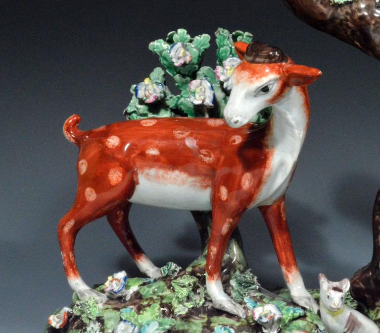 This remarkable rare Staffordshire pearlware large group depicts two large figures of a stag and doe facing each other either side of a central tree trunk triple spill vase is in excellent condition.  A young man playing a horn with sheet music on