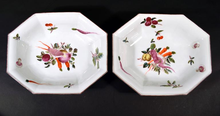 The Chelsea porcelain dishes, after the Meissen, are of an unusual deep octagonal form and are very well painted with a central composition of different fruit and vegetables. One includes a large capped mushroom, carrots and turnips. The other dish