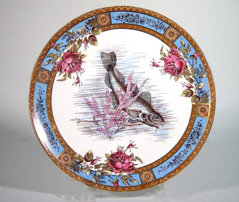 The Wood & Hulme, Garfield Pottery (Waterloo Road, Burslem) plates are decorated with a printed design of a fish amongst seaweed within a border with six bright blue panels decorated with a flowering branch issuing forth roses into the central