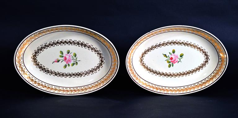 Creamware English pottery pair of botanical 18th-century dishes, Neale Pottery.  The oval dishes are a rich creamy color painted in the interior with a rose stem with an open rose and a rosebud.   Around the inner well is a band of finely