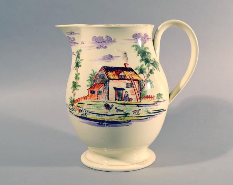 English creamware large jug decorated with farm buildings and farm animals, Staffordshire or Yorkshire, circa 1785.  This charming creamware pottery jug is hand-painted on each side with different rural farm scenes. To one side is a large house