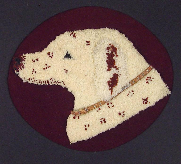 The large stumpwork picture of a dog's head with a leather collar mounted on a red felt ground with a black oval mat within a gilt and black frame.