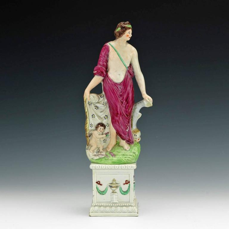 Attributed to Neale & Co,  circa 1790.  The large pearlware early English pearlware figure of Venus or Aphrodite rests her left hand on a dolphin and her right hand holding the open part of her gown to cover Cupid, who rests next to his bow and