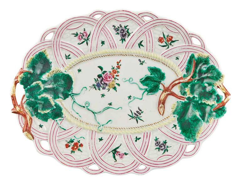 First period Worcester pair of porcelain basket weave leaf dishes,  circa 1758-1760.  The first period Worcester porcelain dishes with moulded strawberry leaf and stem handles, the pierced lattice soles fitted with basketwork, the reserves