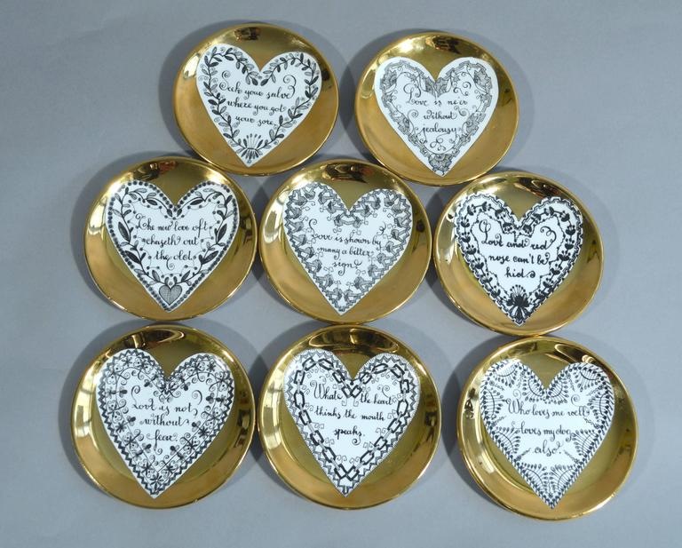 Piero Fornasetti love coasters,  1960s.  Each coaster has a central white heart on a gold ground. Within each heart is a saying about love framed by a different heart shaped border.  The saying or proverbs read as follows  Love is not without