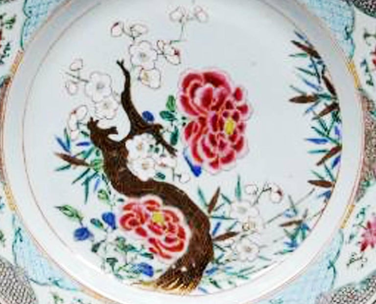Chinese Export famille rose porcelain dishes,  circa 1765-1775.  The pair of Chinese Export famille rose large dishes are finely painted with a flowering branch design with two large red flowers and a branch with blooming small white flowers. The