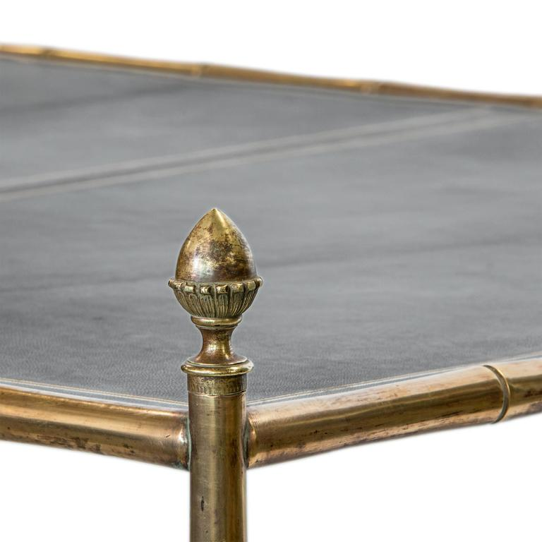 A very unique large brass bamboo coffee table with a three section gold tooled leather top on castors.