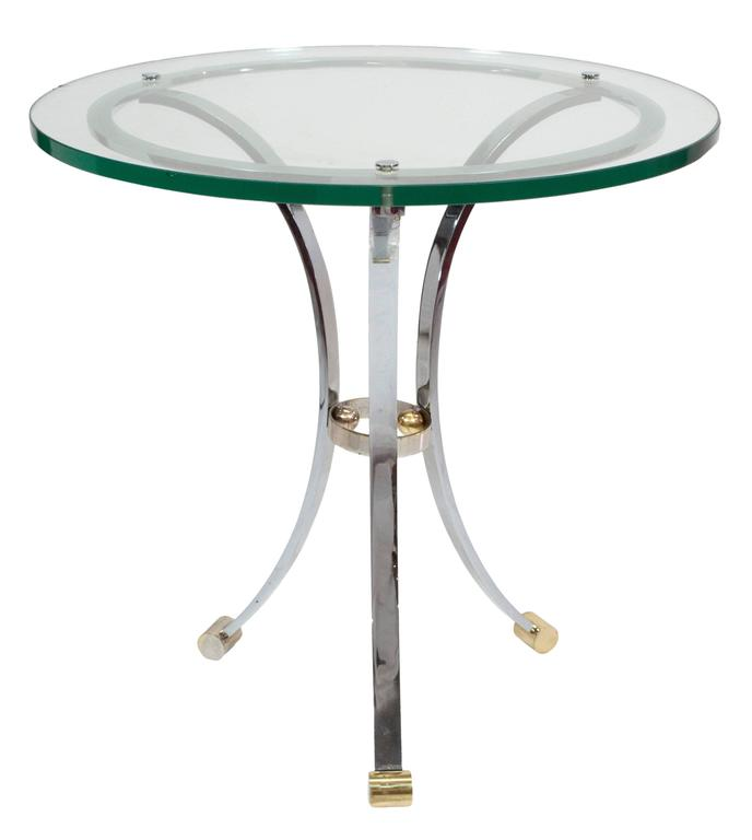A pair of chrome and glass gueridons with brass detail at the feet and center support.