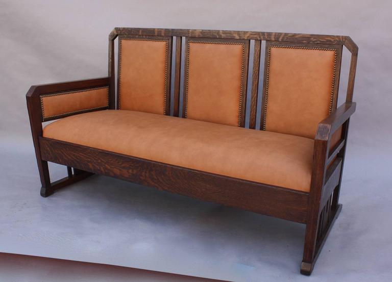 Arts & Crafts period oak settle with new leather upholstery.