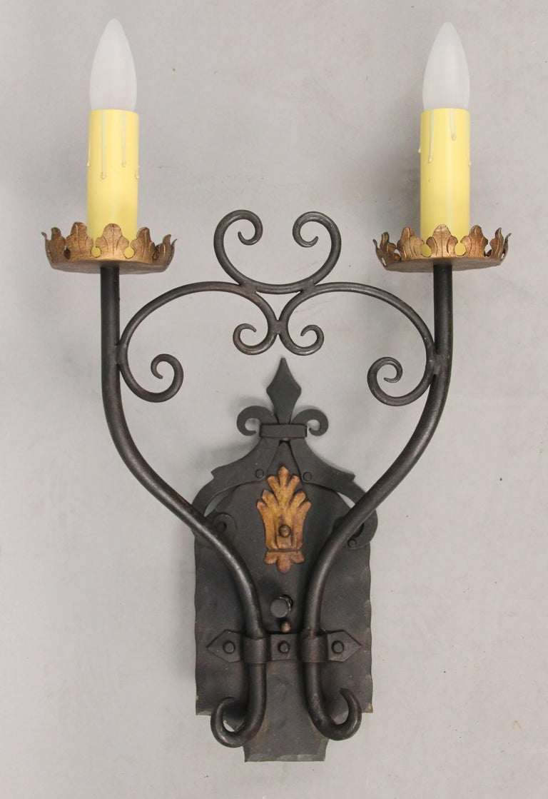 Beautiful and stately 1920s wrought iron two-light sconces. Hard to find high quality pair. Salvaged from local Los Angeles home.