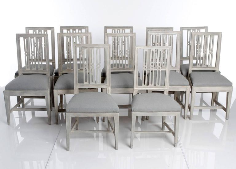 Swedish, late 1700s-early 1800s. Signed Erik Holm, Stockholm master chair-maker 1774-1814. A set of 12 grey-painted Gustavian dining chairs. Open-work backs with simple geometrical shapes. Straight tapered legs with cross stretchers.