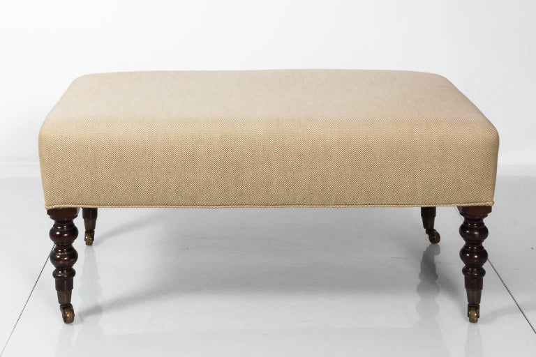 English upholstered bench with ball turned legs on brass castors, circa late 20th century.