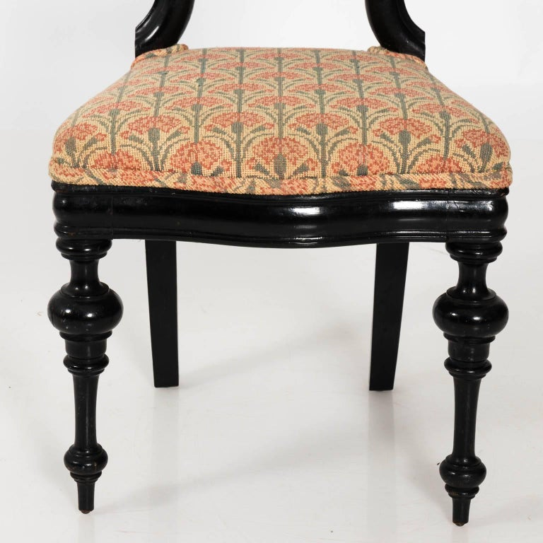 Late 19th century English ebonized wood side chair with a rounded scroll back, trumpet turned legs, and custom upholstered seating.