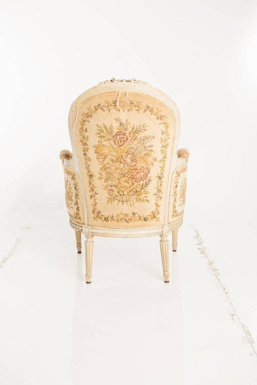 A pair of bergère chairs. Upholstery is decorated with a needlepoint floral motif.