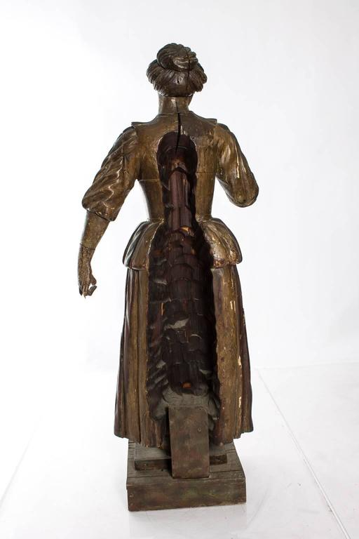 Carved lifesize Victorian figure of a maid. This piece was possibly an architectural element of a larger wooden structure (you can see on the back where the figure was attached), such as staircase.